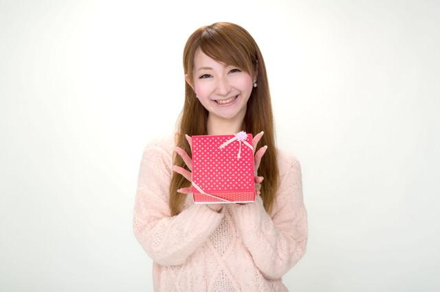 プレゼントを笑顔で渡す女の子の写真