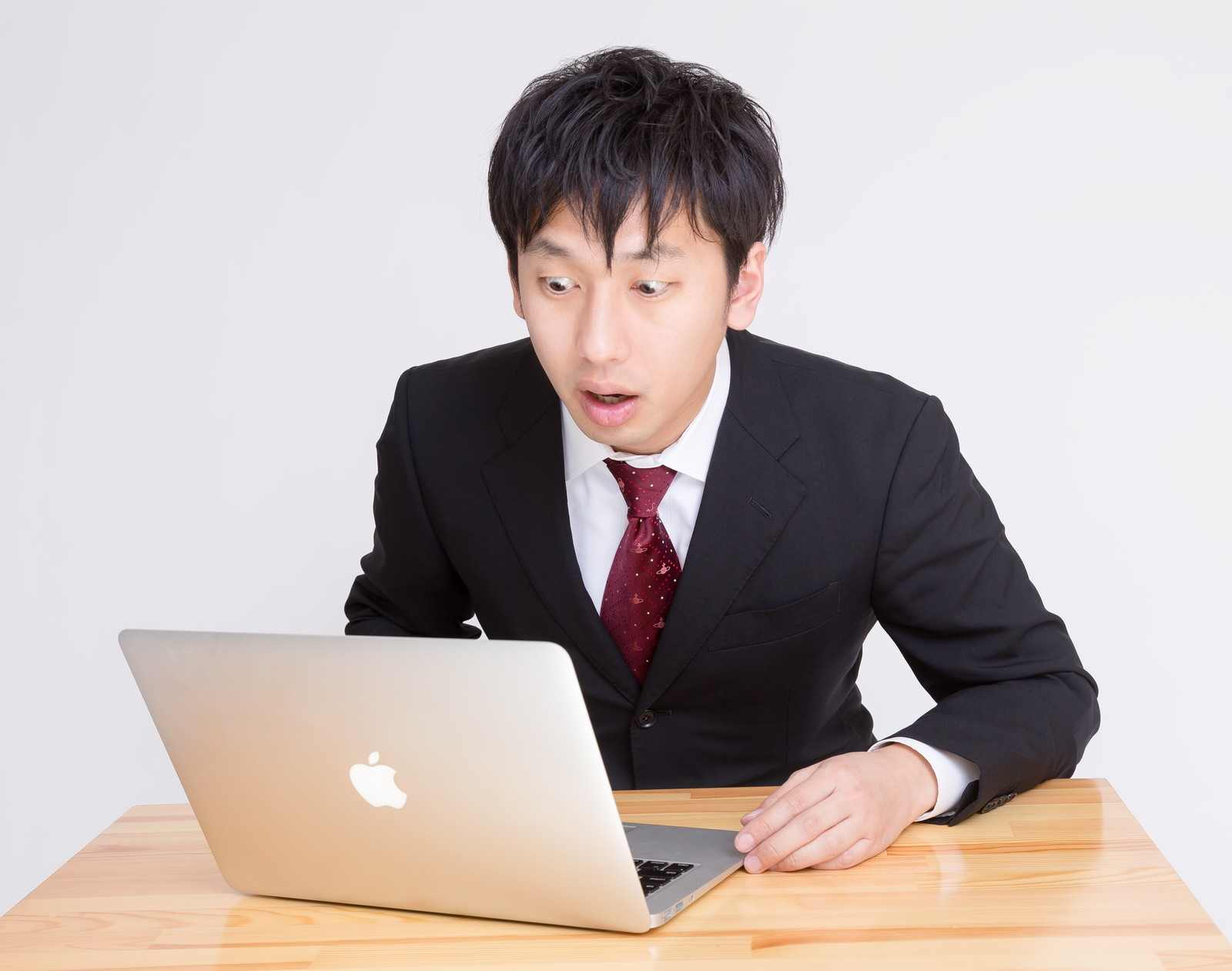 「PCを見て「ヤバいことになった」っと驚く表情のビジネスマンPCを見て「ヤバいことになった」っと驚く表情のビジネスマン」[モデル:大川竜弥]のフリー写真素材
