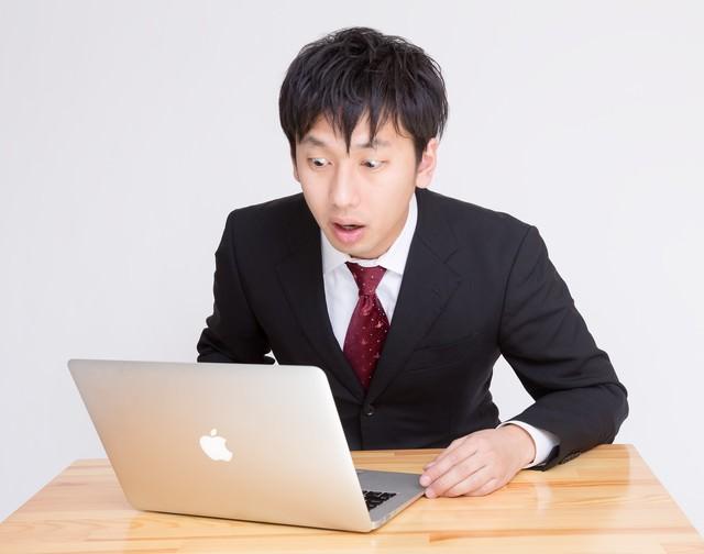 PCを見て「ヤバいことになった」っと驚く表情のビジネスマンの写真