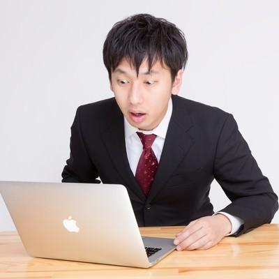 「PCを見て「ヤバいことになった」っと驚く表情のビジネスマン」の写真素材