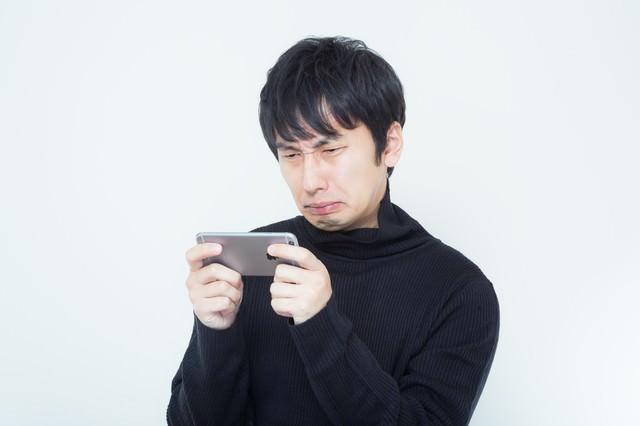 スマホで衝撃動画を見て顔をゆがませる男性の写真