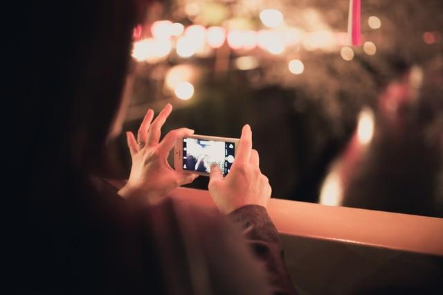 スマホで夜桜を撮影する女性の写真