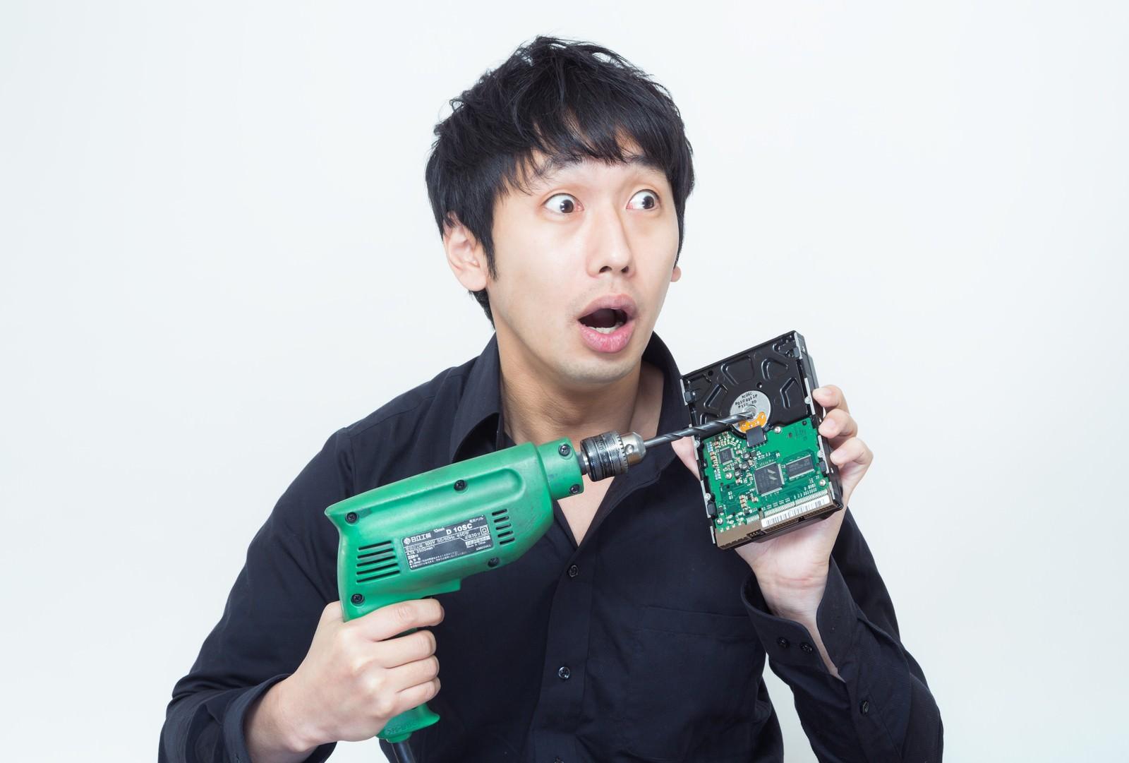 「ドリルでHDDを破壊しようとしたその時、何者かに見つかり焦る男性ドリルでHDDを破壊しようとしたその時、何者かに見つかり焦る男性」[モデル:大川竜弥]のフリー写真素材