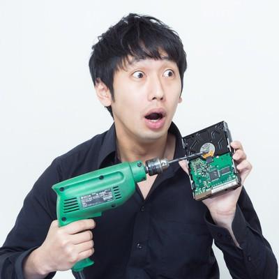 「ドリルでHDDを破壊しようとしたその時、何者かに見つかり焦る男性」の写真素材
