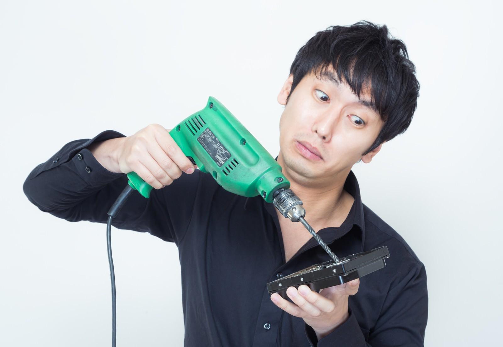 「ドリルを使ってハードディスクのデータを隠滅しようと試みる男性」の写真[モデル:大川竜弥]
