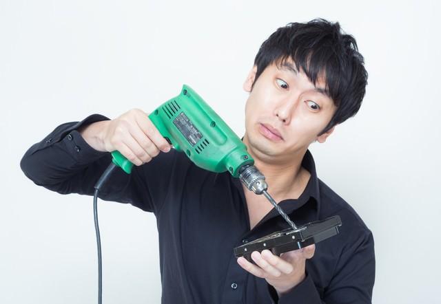 ドリルを使ってハードディスクのデータを隠滅しようと試みる男性の写真