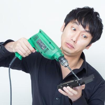 「ドリルを使ってハードディスクのデータを隠滅しようと試みる男性」の写真素材