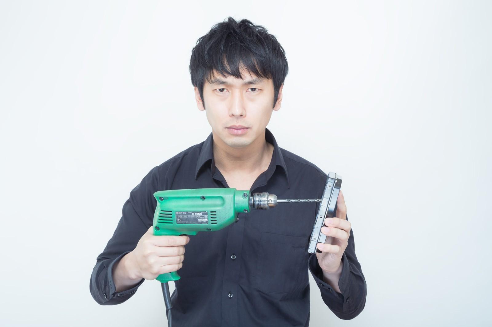 「工業用電気ドリルを使ってHDDに穴を空けようとする男性」の写真[モデル:大川竜弥]