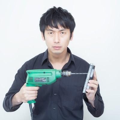 「工業用電気ドリルを使ってHDDに穴を空けようとする男性」の写真素材