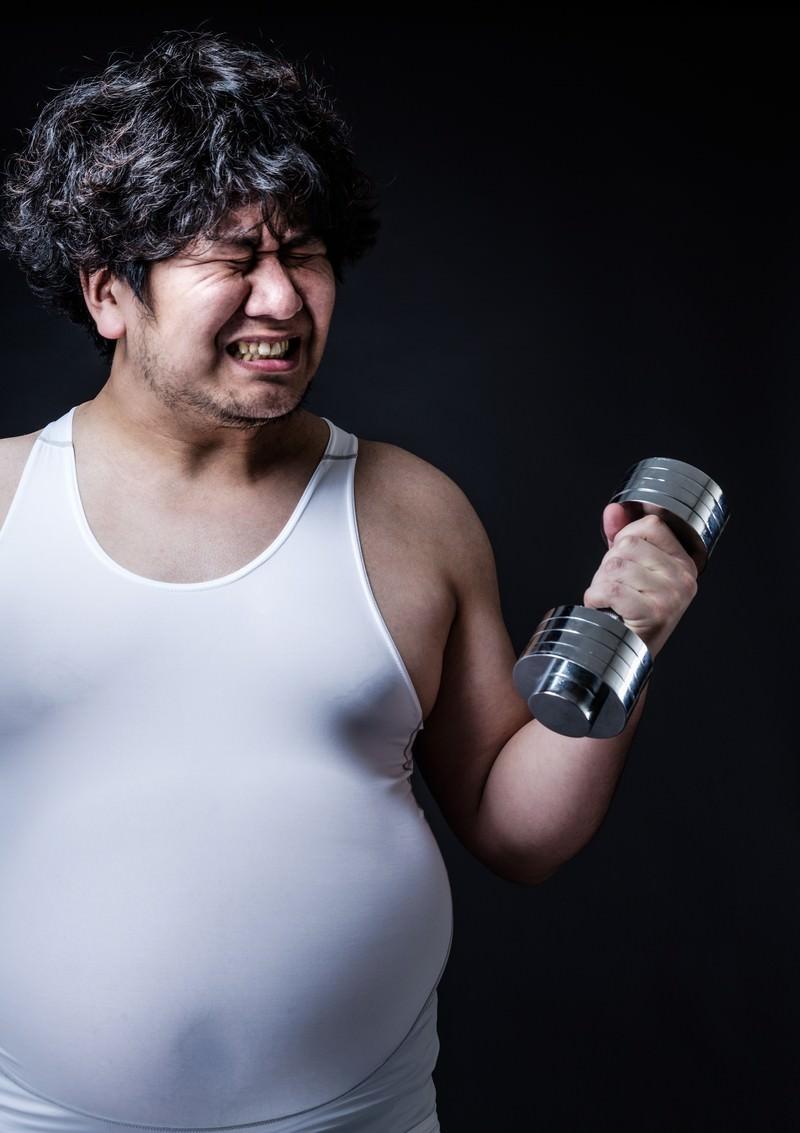「ダンベルよりも贅肉が重そうな肥満男子」の写真[モデル:朽木誠一郎]