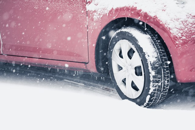 スリップ注意!雪道を走行する車の写真