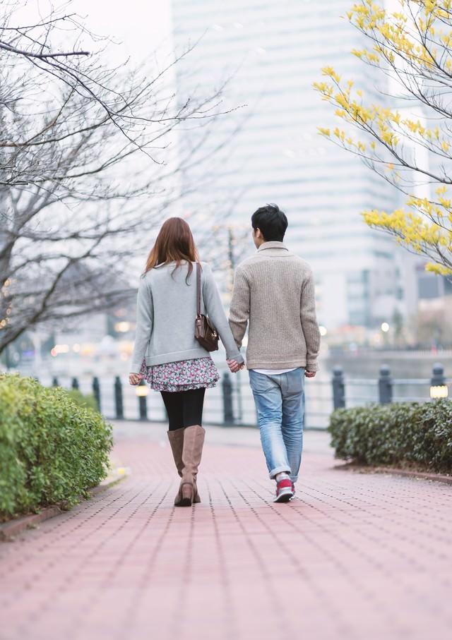 手をつなぎデートする若い男女の写真
