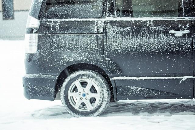 吹雪の中の黒いワゴン車の写真