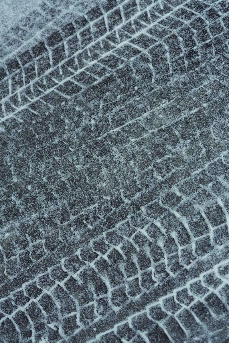「アスファルトに降った雪と轍」の写真