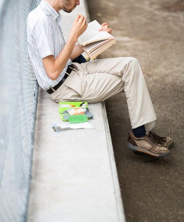 お食事しながら本を読む男性の写真