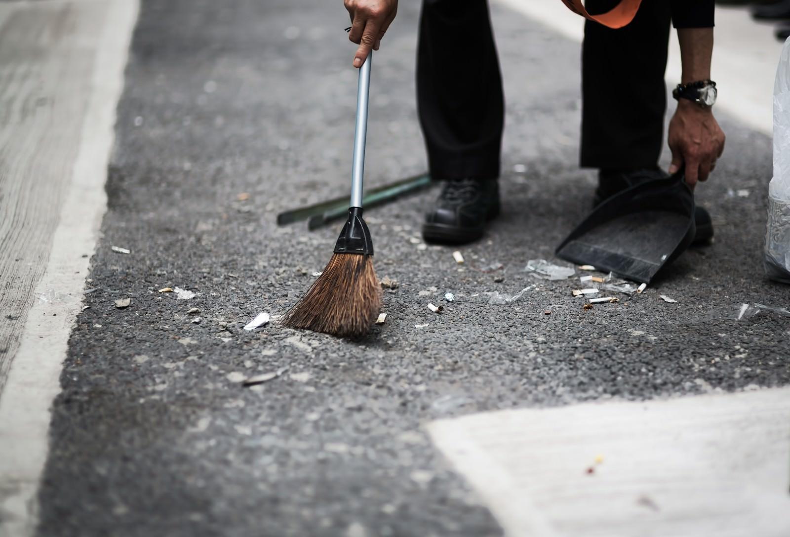 「渋谷の街をチリトリとホウキで清掃する人」の写真