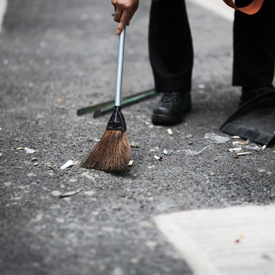 「渋谷の街をチリトリとホウキで清掃する人」の写真素材