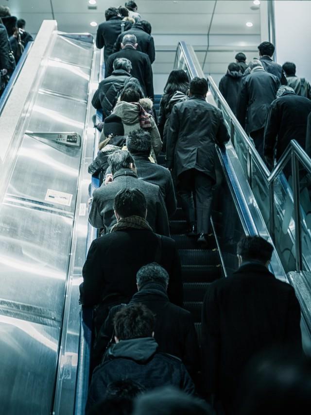 出勤で混みあうエスカレーターの写真