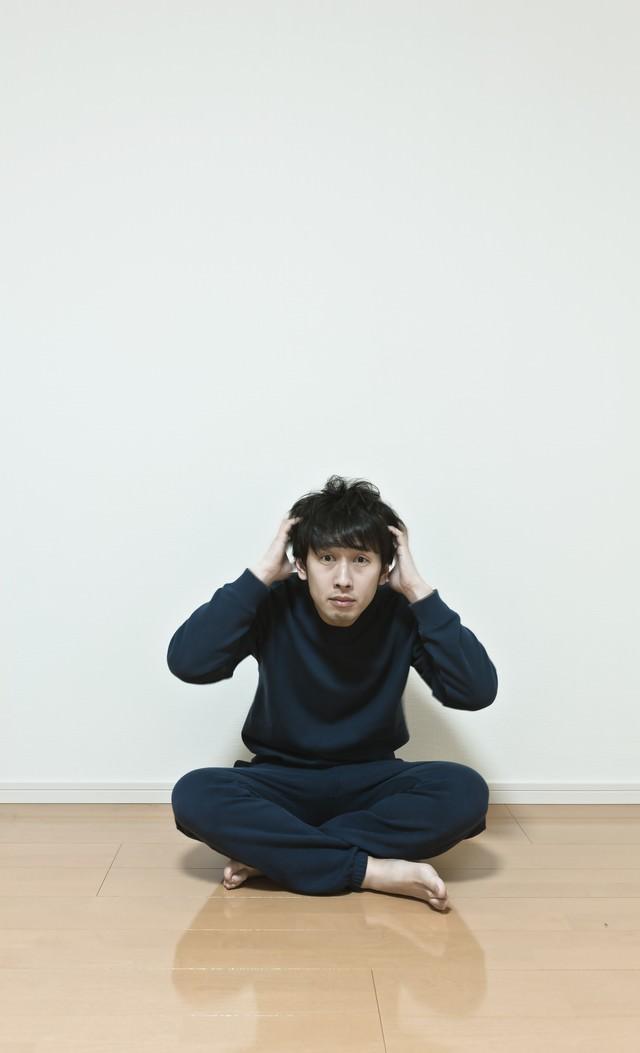ワンルームで頭を抱える無職の男性。今後の不安と葛藤の写真