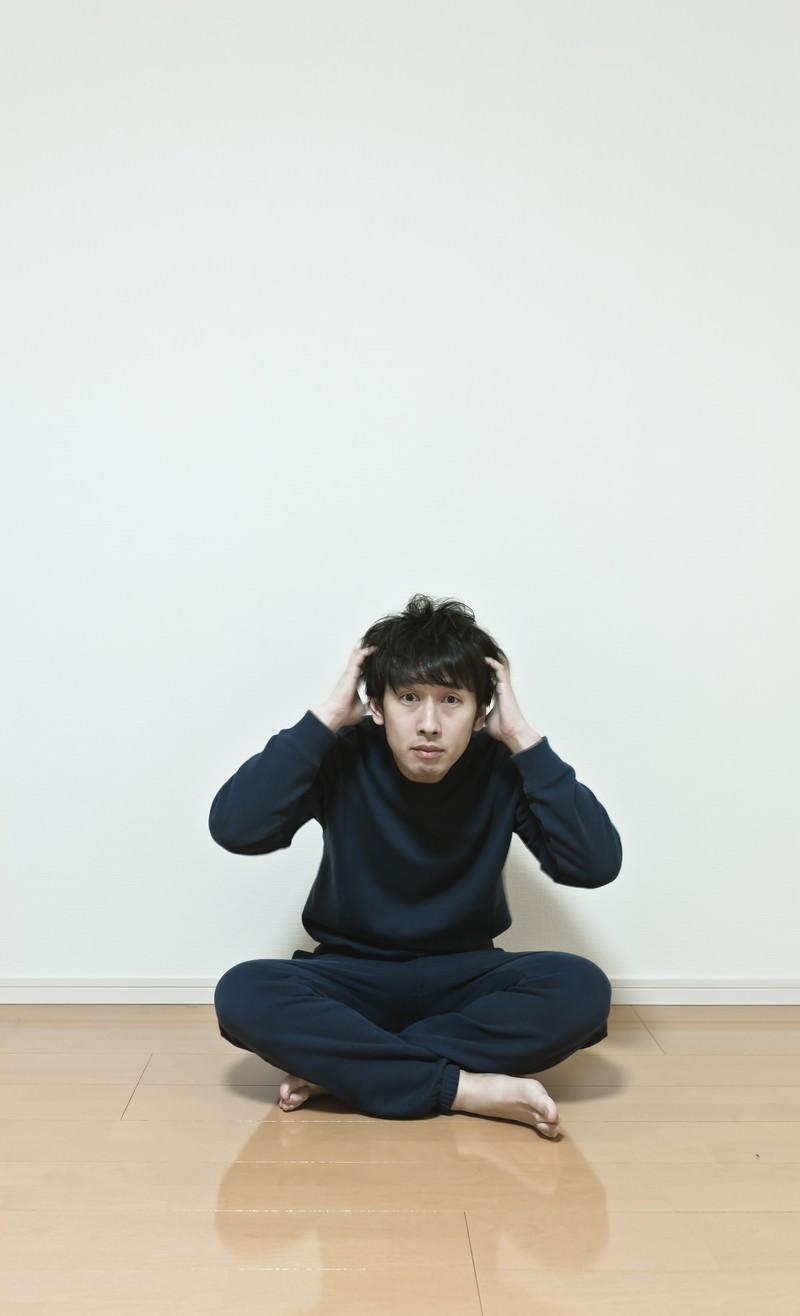 「ワンルームで頭を抱える無職の男性。今後の不安と葛藤」の写真[モデル:大川竜弥]