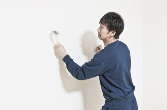 ハンマーで壁を連打するスウェット姿の男性の写真