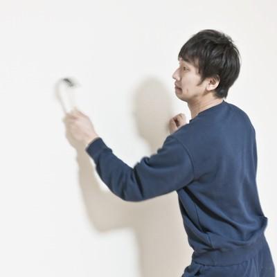 「ハンマーで壁を連打するスウェット姿の男性」の写真素材