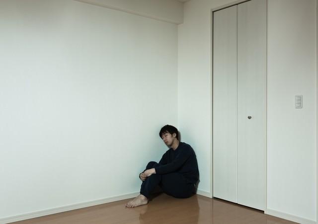 部屋の隅っこで独り寂しく寝落ちする男性の写真
