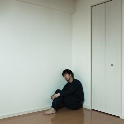 「部屋の隅っこで独り寂しく寝落ちする男性」の写真素材