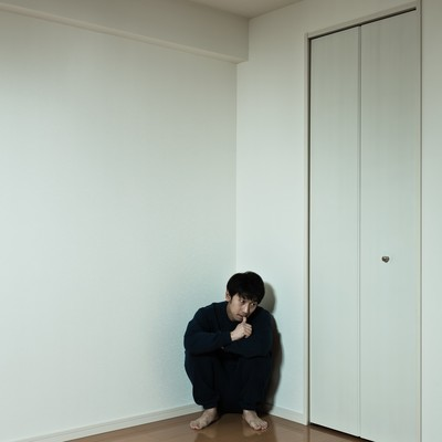 「部屋の隅っこに縮こまるスウェット姿の男性」の写真素材