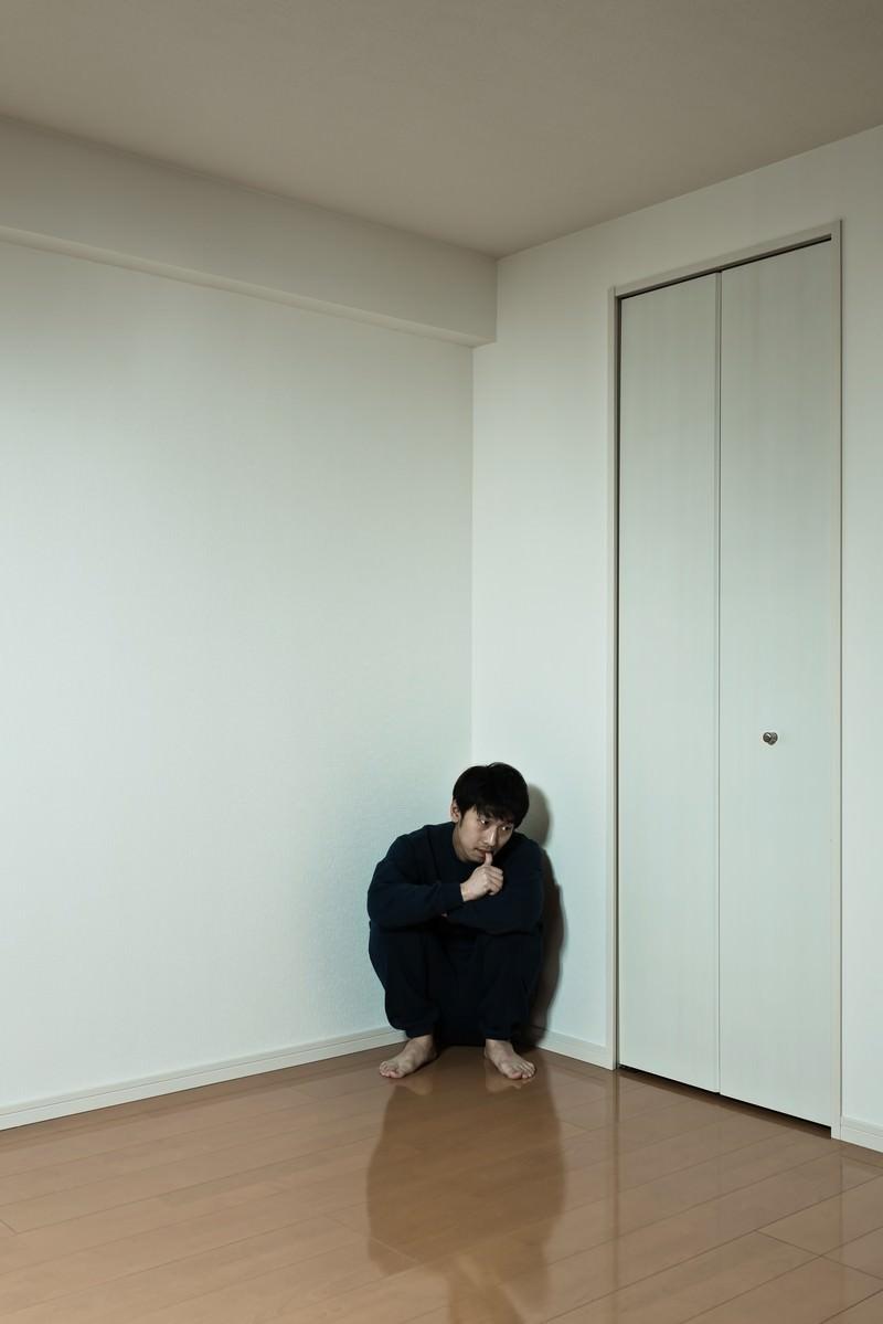 「部屋の隅っこに縮こまるスウェット姿の男性」の写真[モデル:大川竜弥]