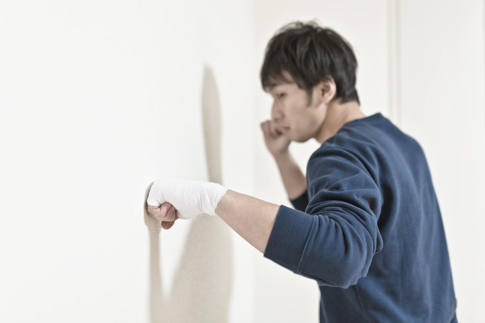 「包帯をしてまで壁を殴り続ける男性」の写真[モデル:大川竜弥]
