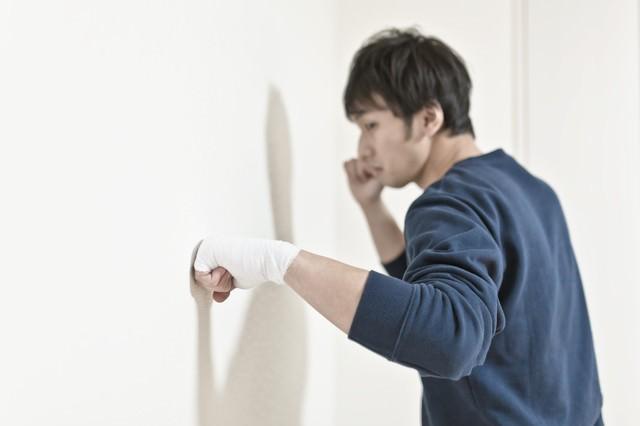 包帯をしてまで壁を殴り続ける男性の写真