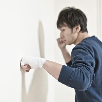 「包帯をしてまで壁を殴り続ける男性」の写真素材