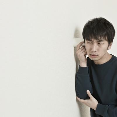 紙コップを耳に当て、隣の会話を盗み聞きする男性の写真