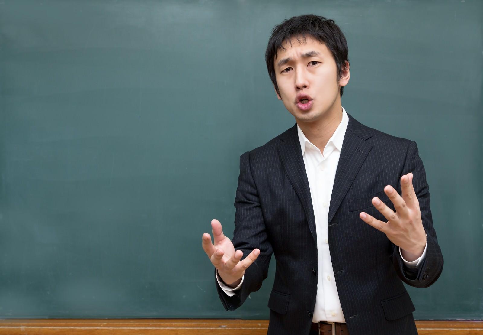 「黒板の前で思いを伝える塾の講師」の写真[モデル:大川竜弥]