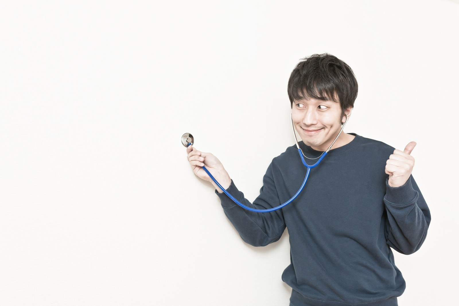 壁に聴診器を当てて、確かな手ごたえを感じる男性のフリー素材