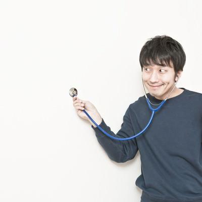 「壁に聴診器を当てて、確かな手ごたえを感じる男性」の写真素材
