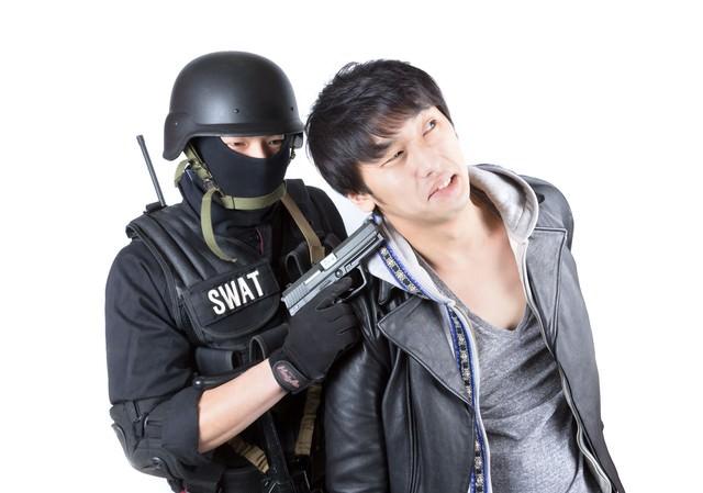 身柄を拘束された男性の写真