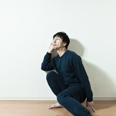 「隣の会話を盗み聞ぎするスウェット姿の男性」の写真素材