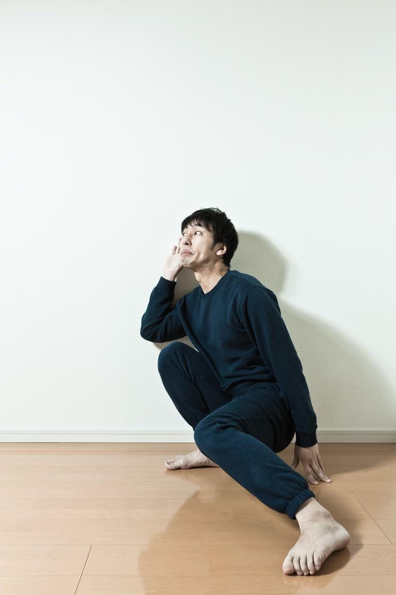 「隣の会話を盗み聞ぎするスウェット姿の男性」の写真[モデル:大川竜弥]