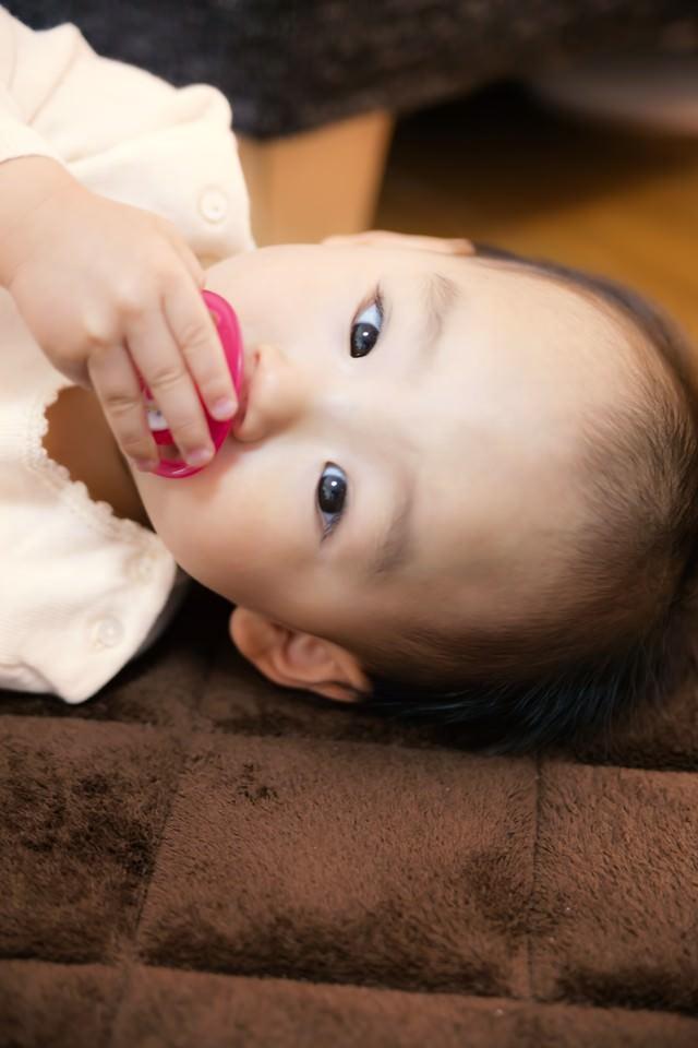 おしゃぶりを手で触る赤ちゃんの写真