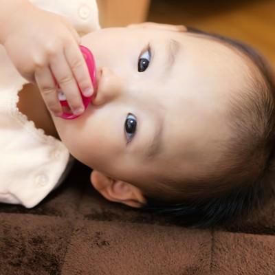 「おしゃぶりを手で触る赤ちゃん」の写真素材