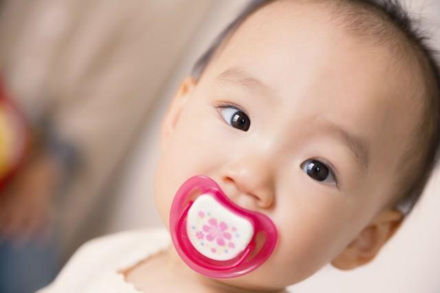 おしゃぶりを咥えた赤ちゃんの写真