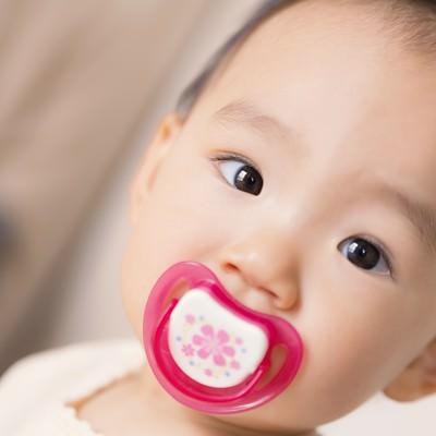 「おしゃぶりを咥えた赤ちゃん」の写真素材