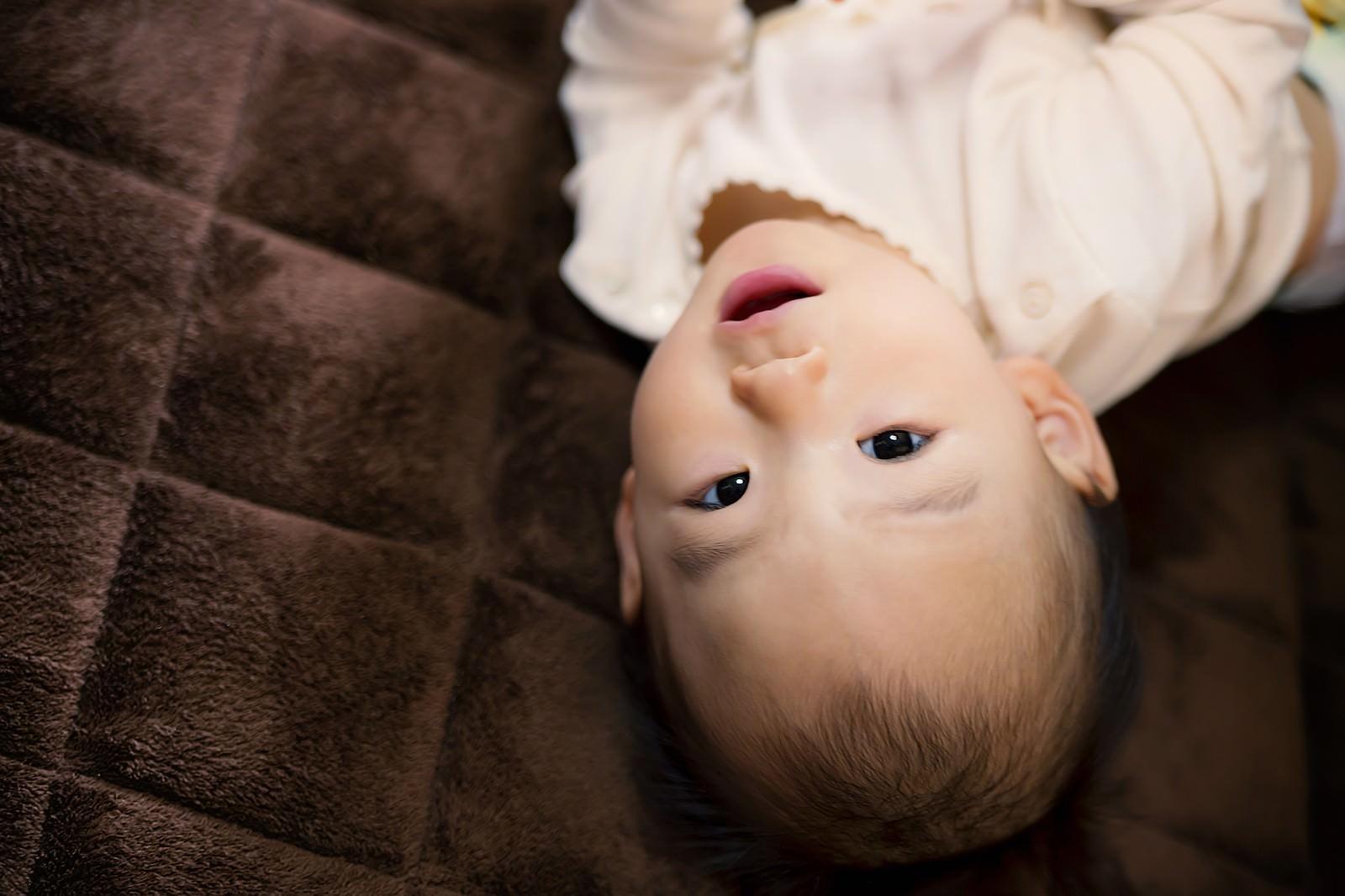 「床に寝転び微笑む赤ちゃん」の写真[モデル:あんじゅ]