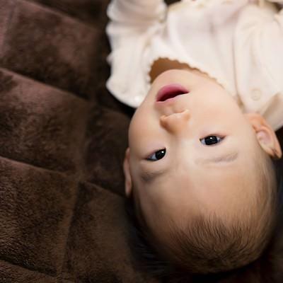 床に寝転び微笑む赤ちゃんの写真
