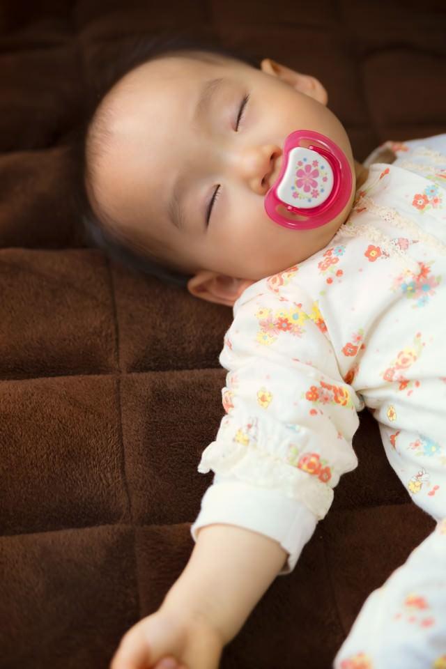 おしゃぶりを咥えながら眠る赤ちゃんの写真