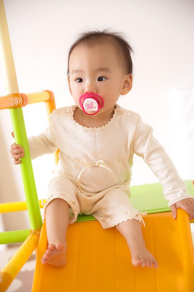 滑り台につかまる赤ちゃんの写真