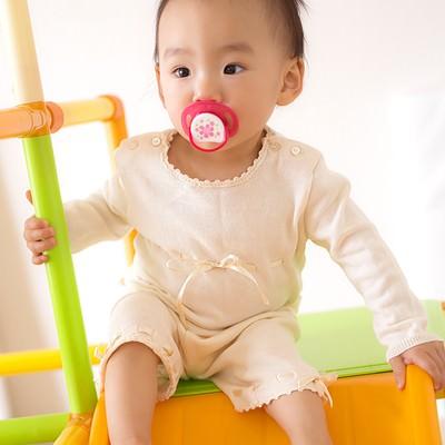 「滑り台につかまる赤ちゃん」の写真素材