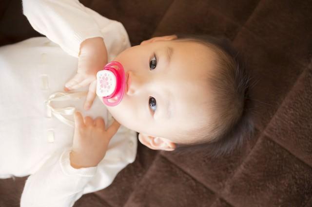 おしゃぶりを咥えて横になる赤ちゃんの写真